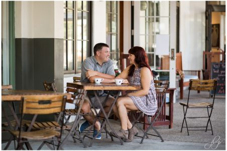 Couple sitting together drinking coffee in front of Amavida Coffee Shop in Rosemary Beach, Florida.